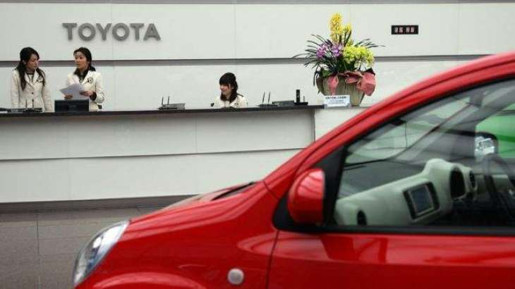 Toyota profit tumbles on strong yen, but lifts full-year view
