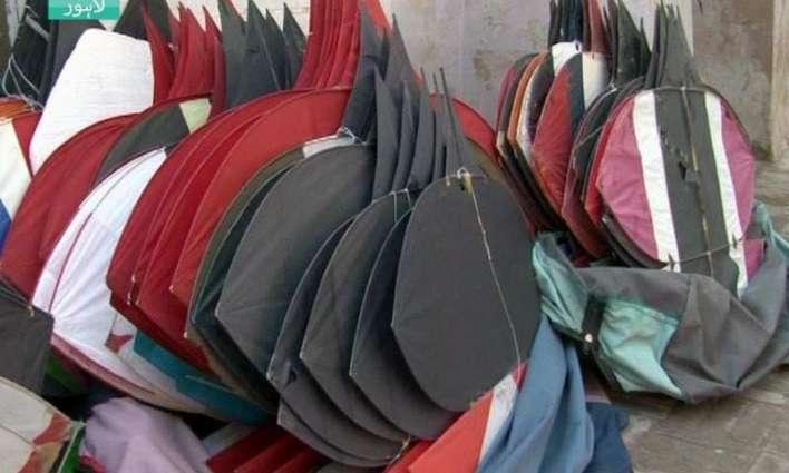 One kite-seller, two kite-fliers held