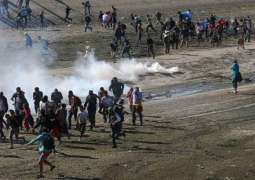 Tear gas fired as dozens of migrants try illegal crossing to US