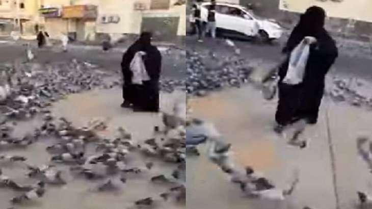 شاھد : امرأة سعودیة تطعم الحمام في شوارع مکة المکرمة و تدع اللہ أن یرفع البلاء عن العالم