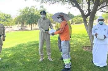 """شرطة دبي و """"روح الاتحاد"""" يوزعان قبعات مظلية  على العمال"""